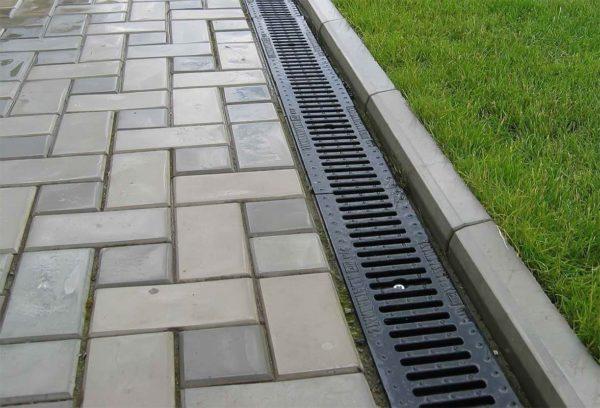 Дождеприемник для ливневой канализации рядом с брусчаткой