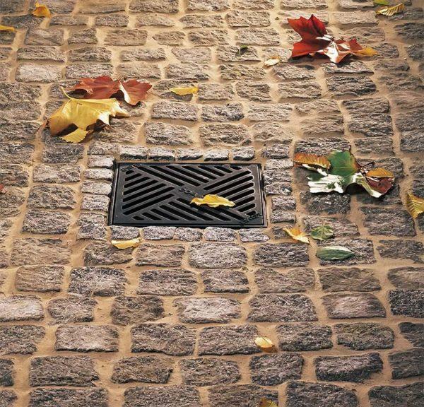 Дождеприемник для ливневой канализации и листья вокруг